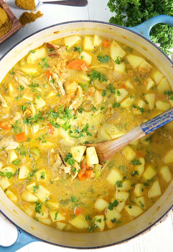 A close up shot shows the ingredients of mulligatawny soup in a large pot.