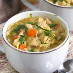 Two white mugs are filled with chicken noodle soup.
