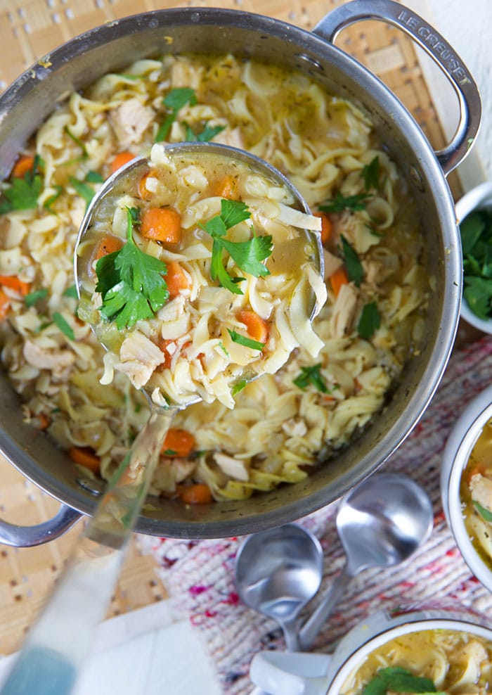 A large ladle is scooping out portions of chicken noodle soup from a big pot.
