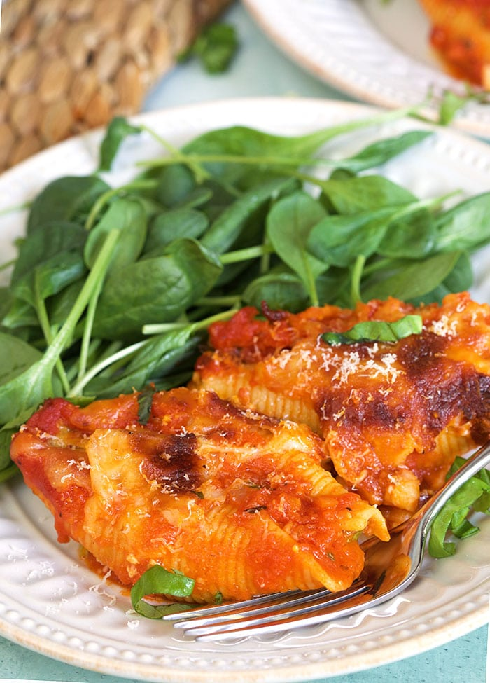 A serving of stuffed shells is on a white plate, next to a helping of spinach leaves.