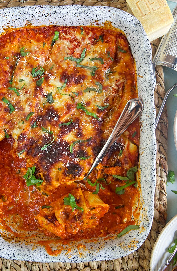 A large baking dish contains a fully baked dinner serving of stuffed shells.