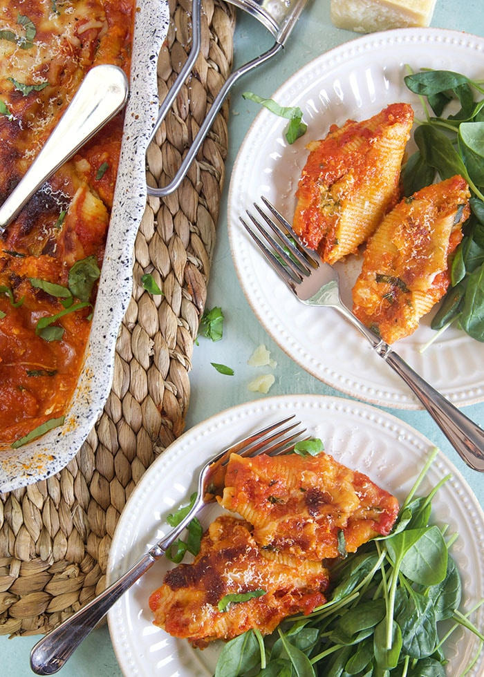 Two white plates contain servings of stuffed shells and spinach leaves.