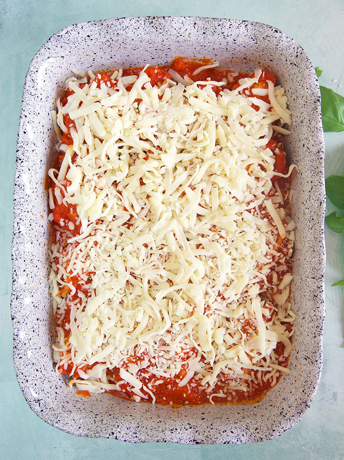 Shredded cheese covers the red sauce and shells in the baking dish.