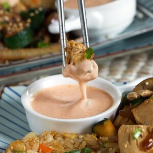 A piece of chicken is dipped into yum yum sauce with chopsticks.