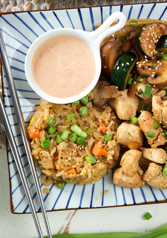 Yum yum sauce is presented on a plate next to a full hibachi meal.