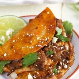 Two birria tacos are placed on a white plate with a slice of fresh lime on the side.