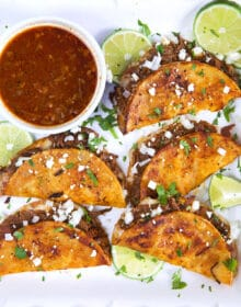 Birria Tacos on a white platter with a bowl of sauce and limes.
