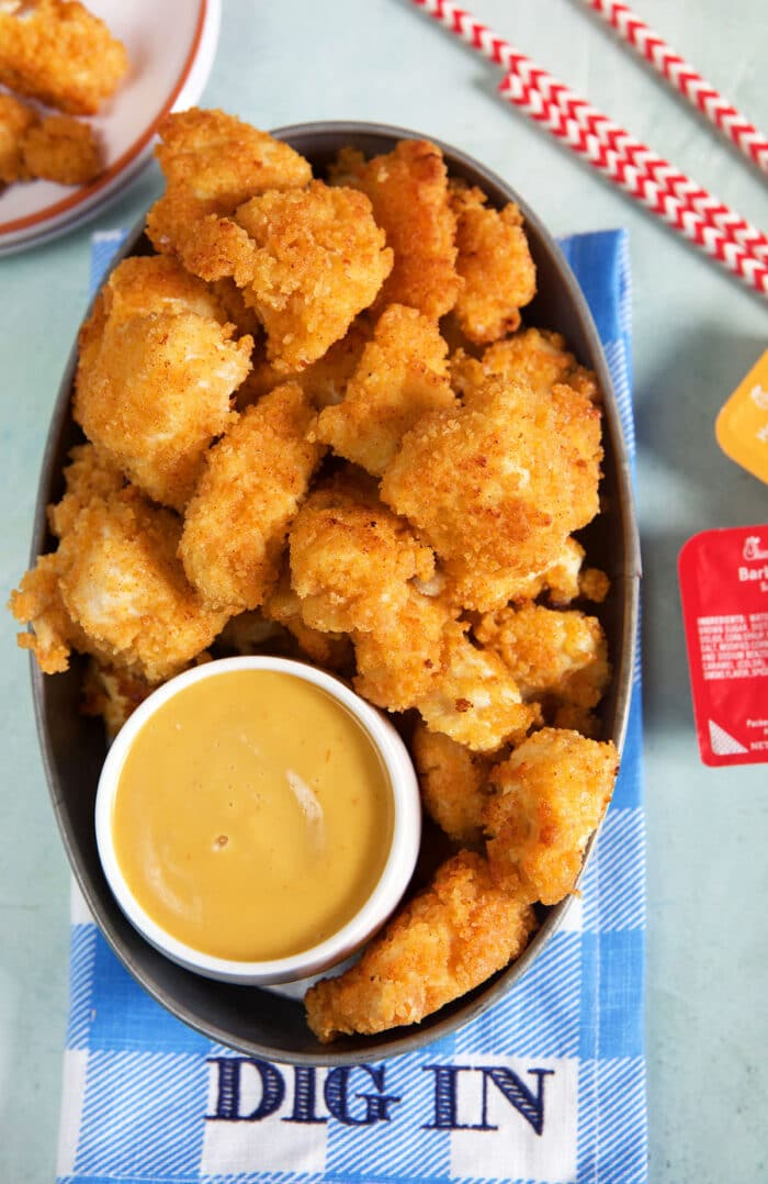 Sauce and nuggets are on an oval shaped plate.