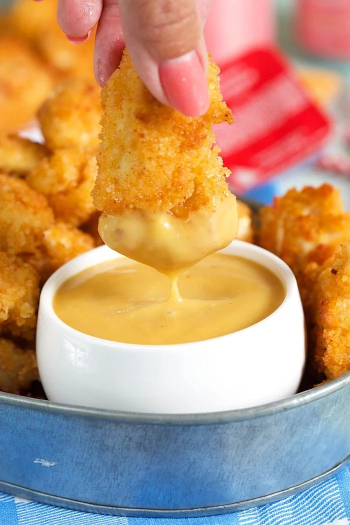 A chicken nugget is covered in yellow sauce.