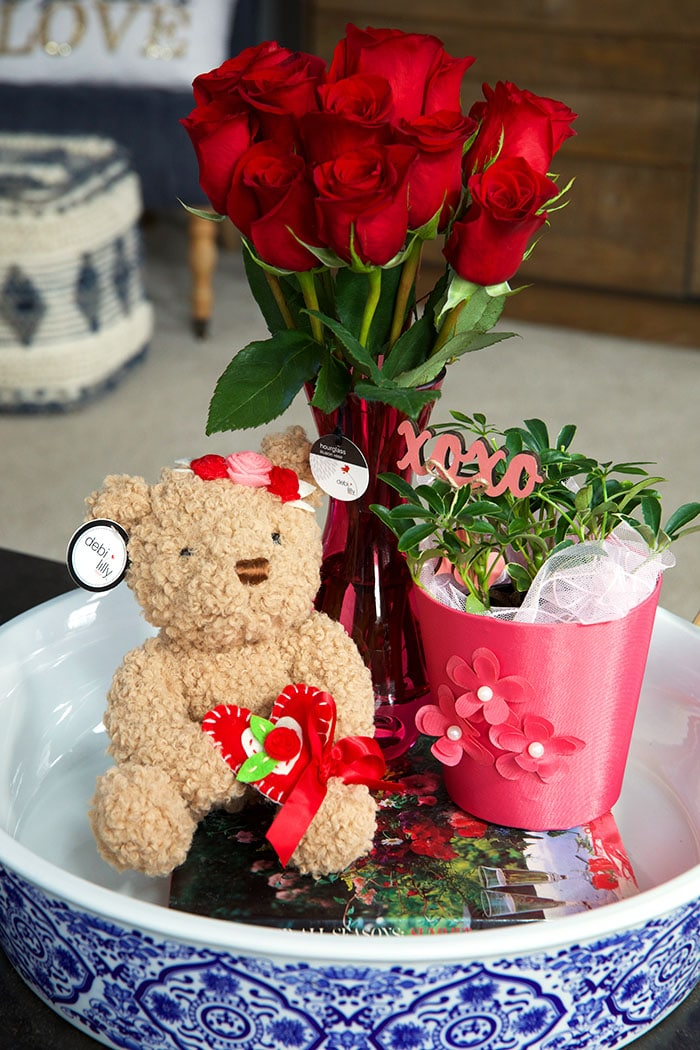 teddy bear and roses in a blue and white ceramic tray.