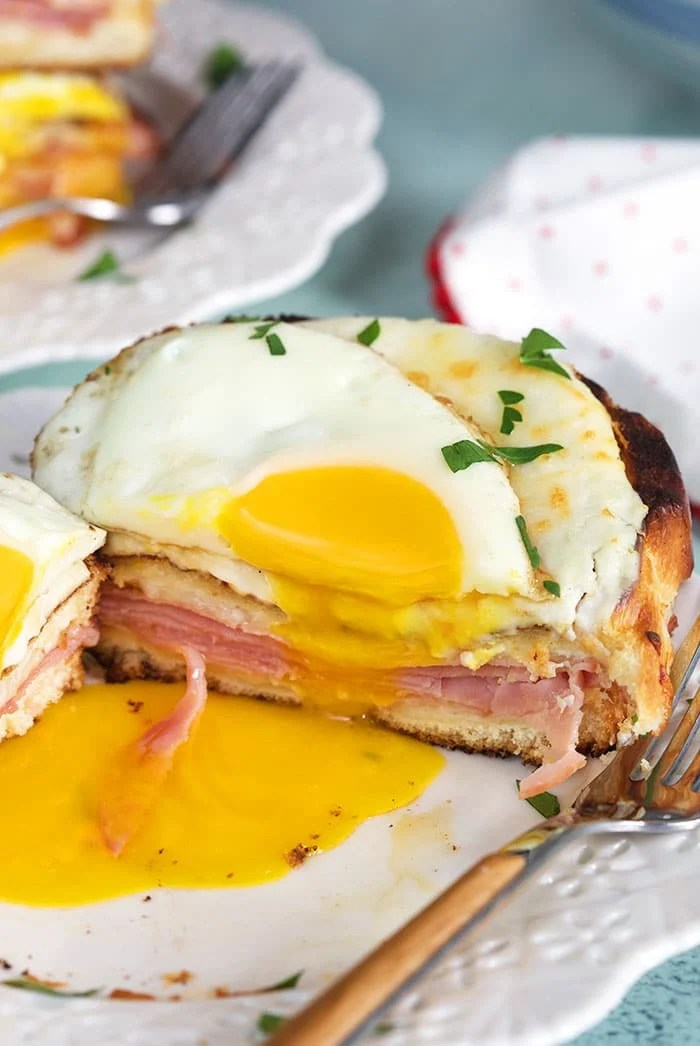 Croque madame cut in half on a white plate.
