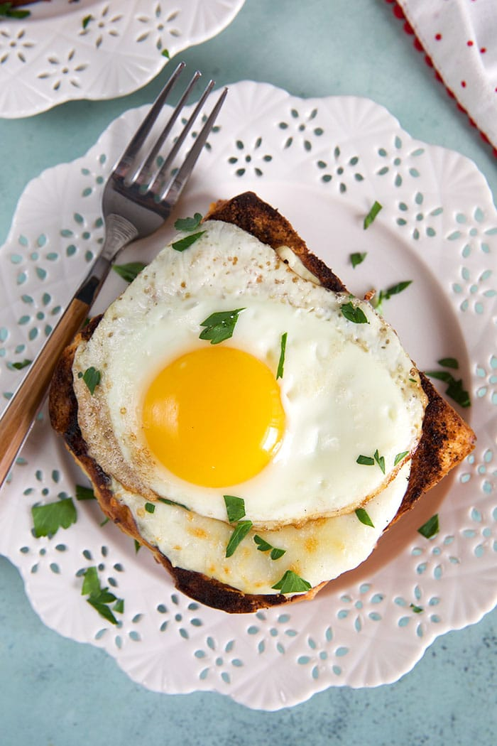 croque madame on a white plate with a fork on a blue background.