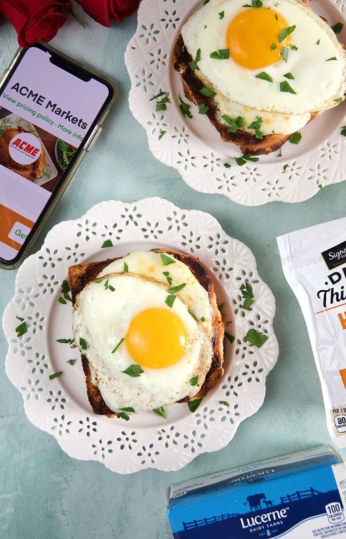 two croque madame sandwiches on white Lacey plates with an iPhone on a blue background.