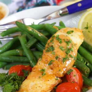 Halibut is ready to eat on a plate with green beans and tomatoes.