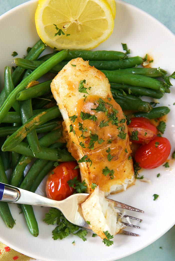 A piece of cooked halibut sits on top of green beans and tomatoes on a white plate.
