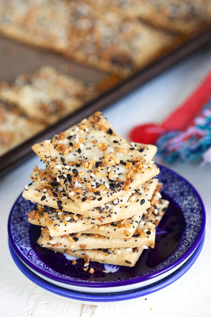 A stack of crackers is placed on a small navy blue plate.