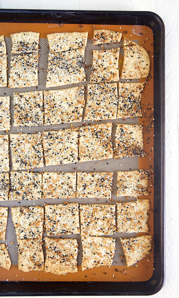 Many pieces of everything crackers are spread out on a large lined baking sheet.
