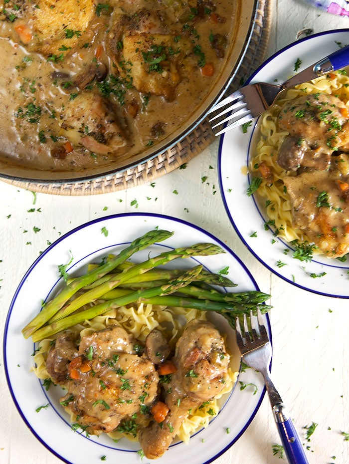 A plate of chicken fricassee sits next to a large, full dutch oven.