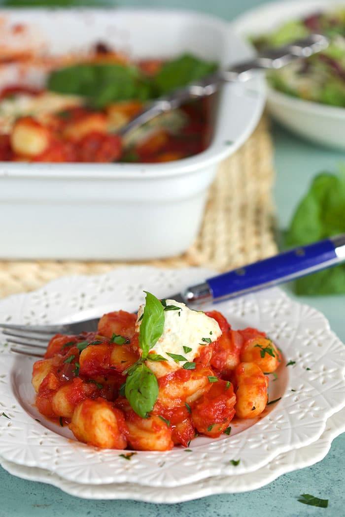 Fresh basil garnishes a serving of gnocchi alla sorrentina.