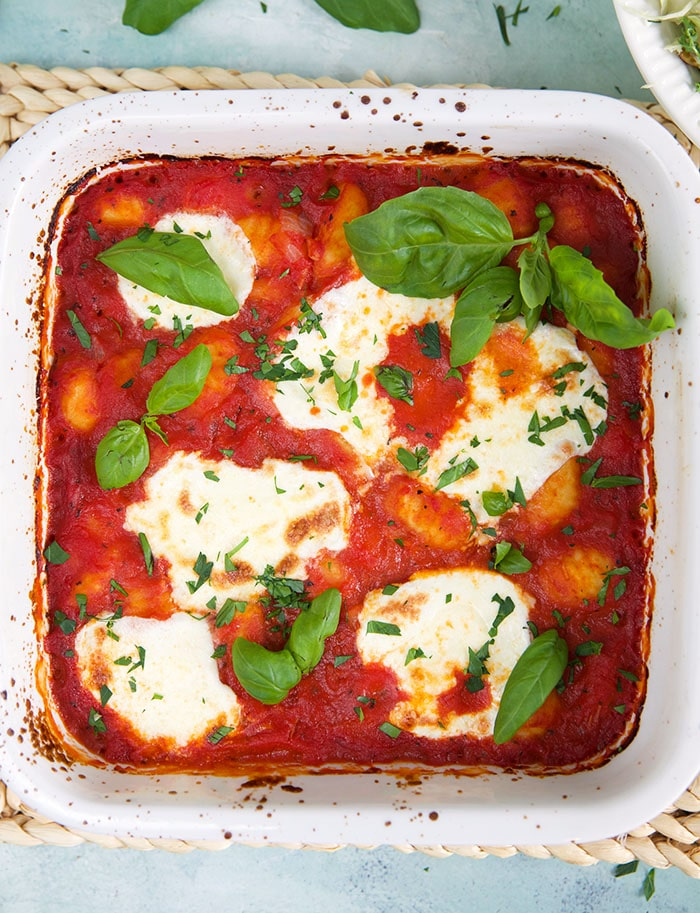 A square baking pan contains red sauce, gnocchi, white cheese and fresh basil.