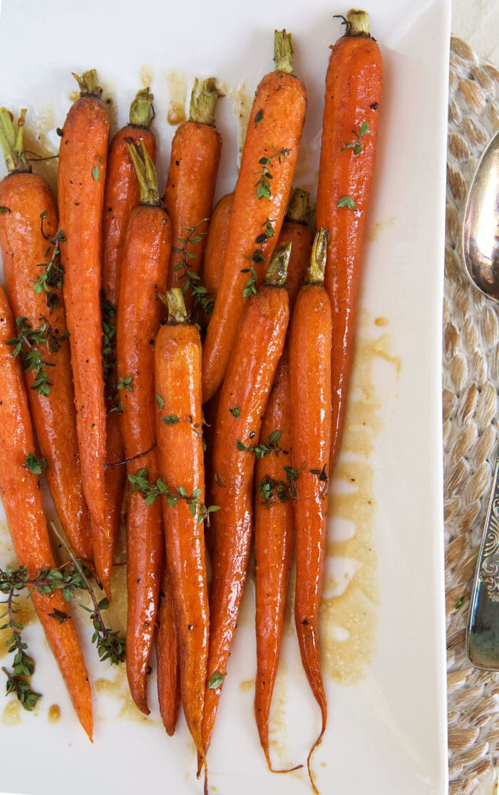 Roasted balsamic carrots are on a white platter, ready to be served.