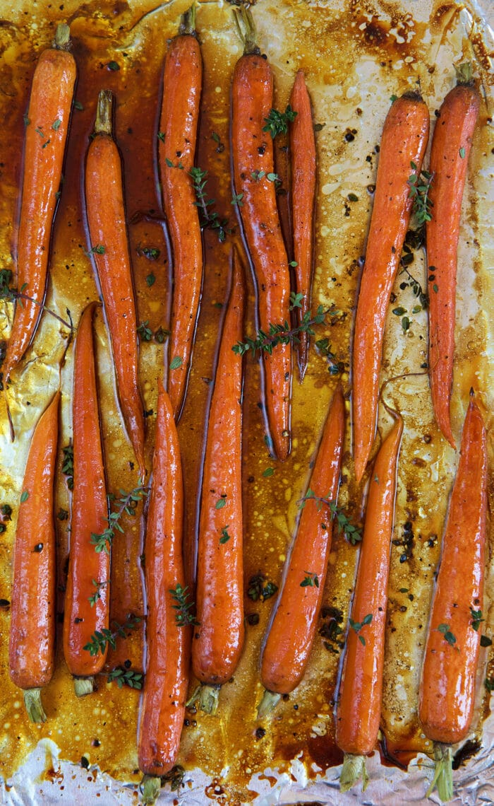 Carrots are spread out evenly on a baking sheet.