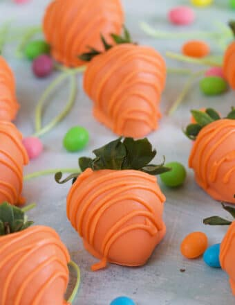 Orange drizzled strawberries are placed on a white surface.