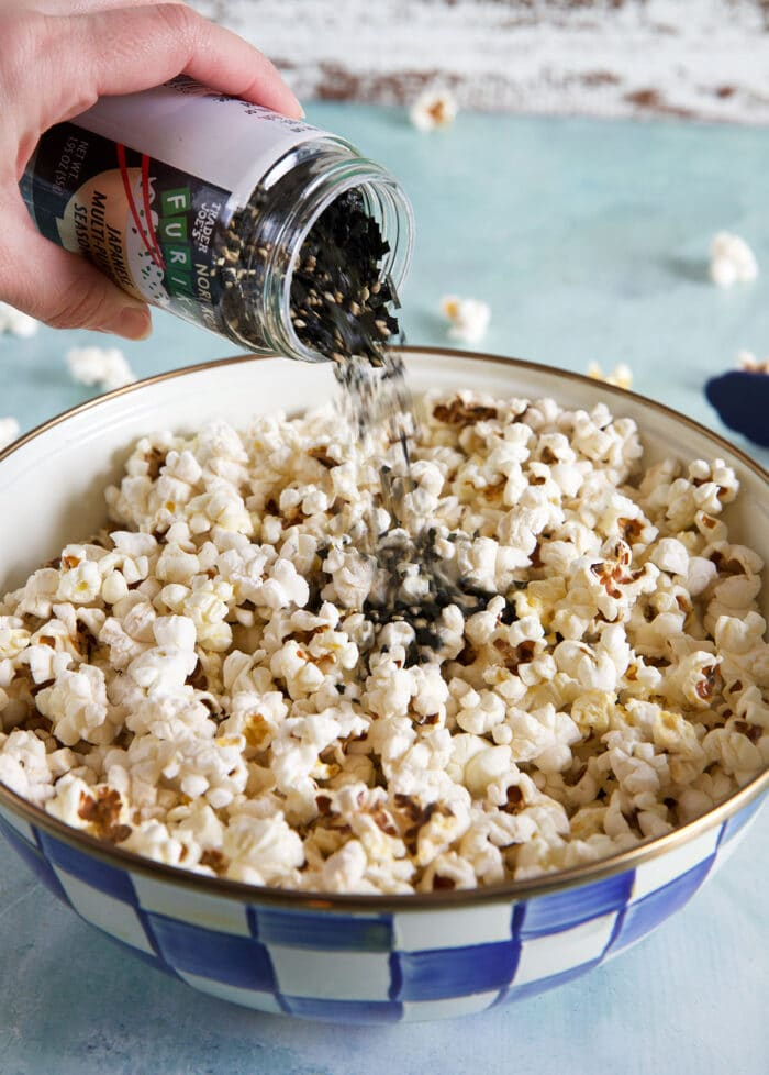 Furikake is being added to the buttery popcorn.