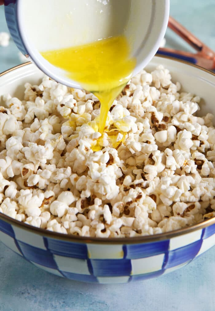 Melted butter is being poured over the popcorn.