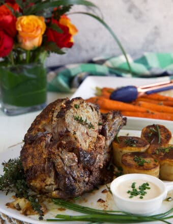 A prime rib roast is presented on a white plate.