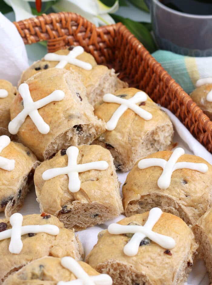 Hot Cross buns in a wicker tray with a cup of coffee in the background.