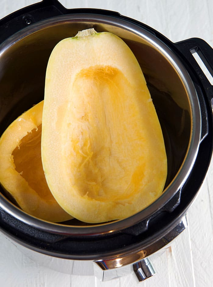 Two seedless squash halves are placed in the Instant Pot.