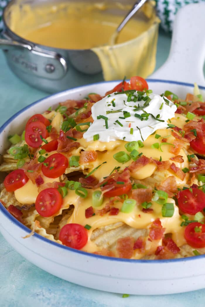 A full plate of nachos is placed by a hot pot of melted beer cheese.