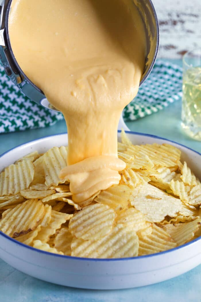 Beer cheese sauce is being poured on to potato chips.