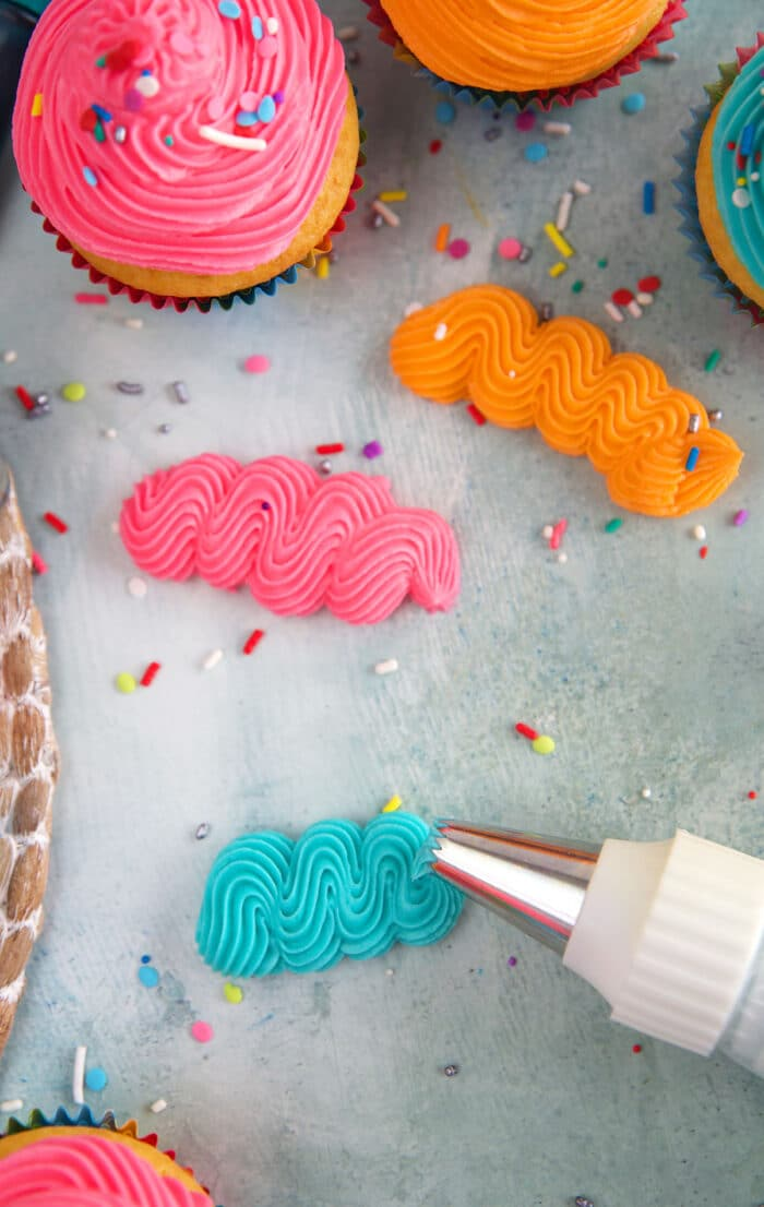 Squiggles of frosting are piped onto a parchment paper.