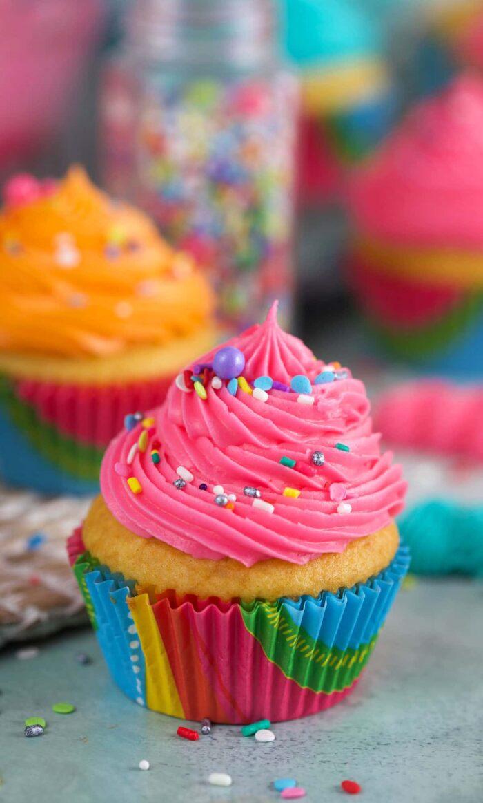A pink cupcake is sprinkled with rainbow sprinkles.