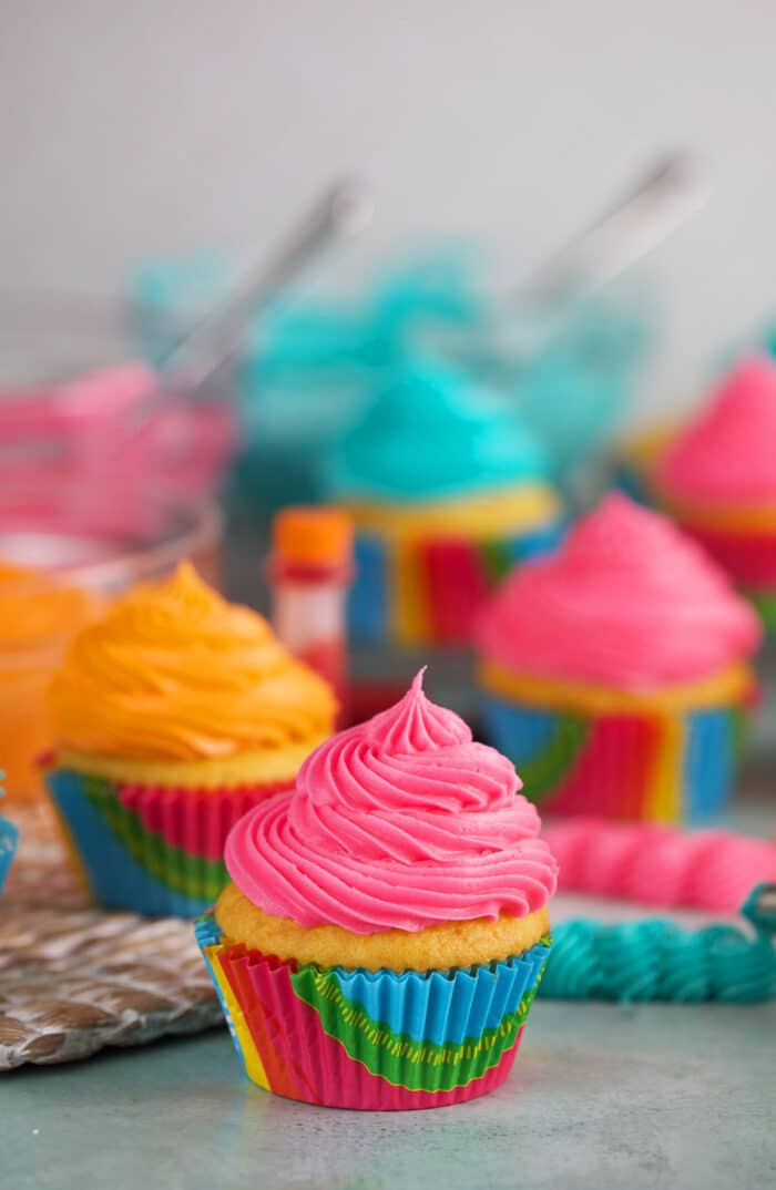 Pink, blue, and orange frosted cupcakes are presented on a countertop.