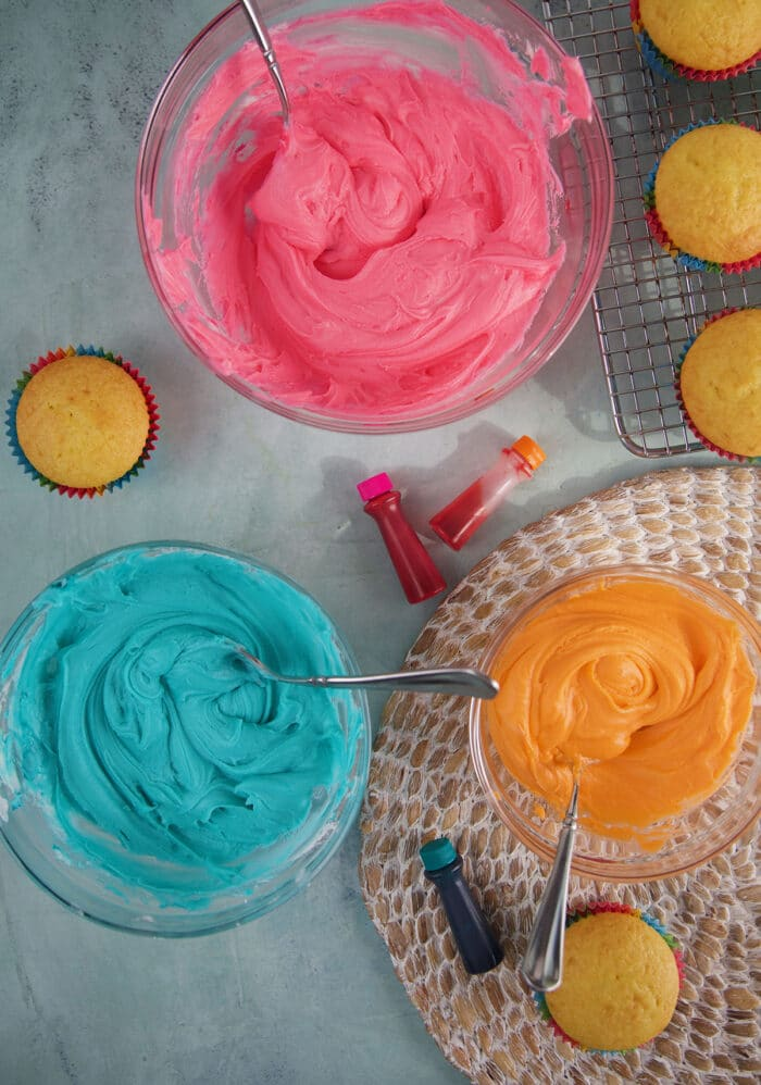Three bowls contain blue, pink, and orange frosting.