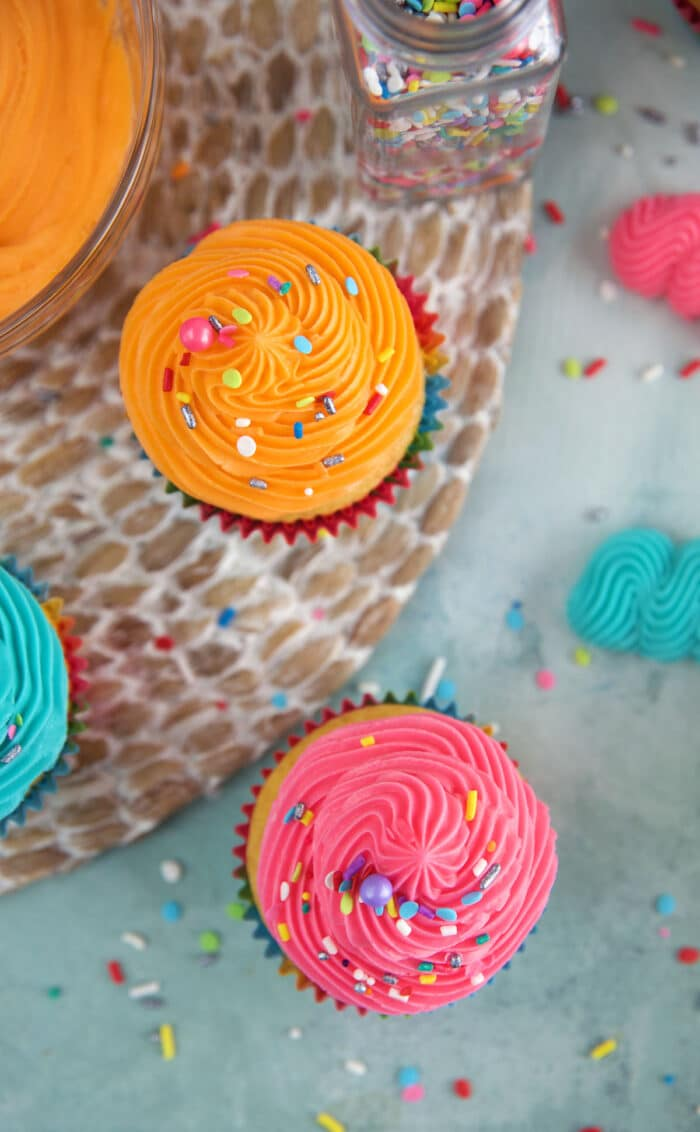 Several frosted valilla cupcakes are placed on a countertop.