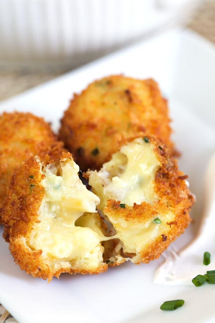 A potato croquette has been split in half, showing the creamy potato interior.