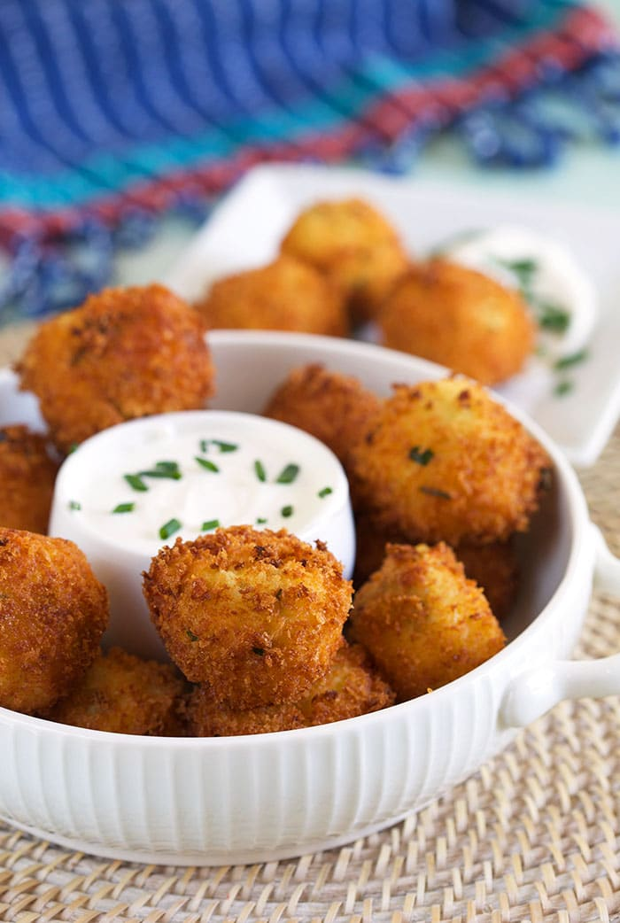 A large white bowl filled with croquettes is ready to be served.