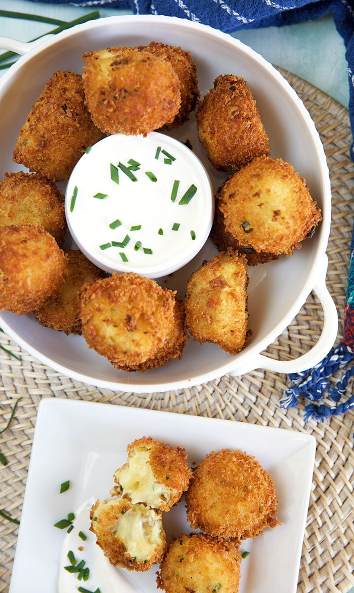 A bowl full of croquettes sits next to a plate with several croquettes.