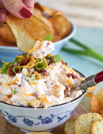 A potato chip is scooping up a small dollop of million dollar dip.