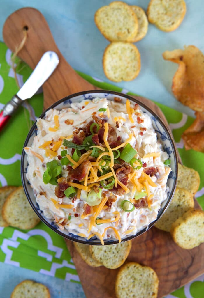 A bowl of creamy dip is placed on a wooden surface with crackers and a dip knife.