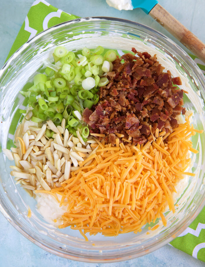 Almonds, cheese, bacon and green onions are placed on top of mayonnaise in a glass bowl.