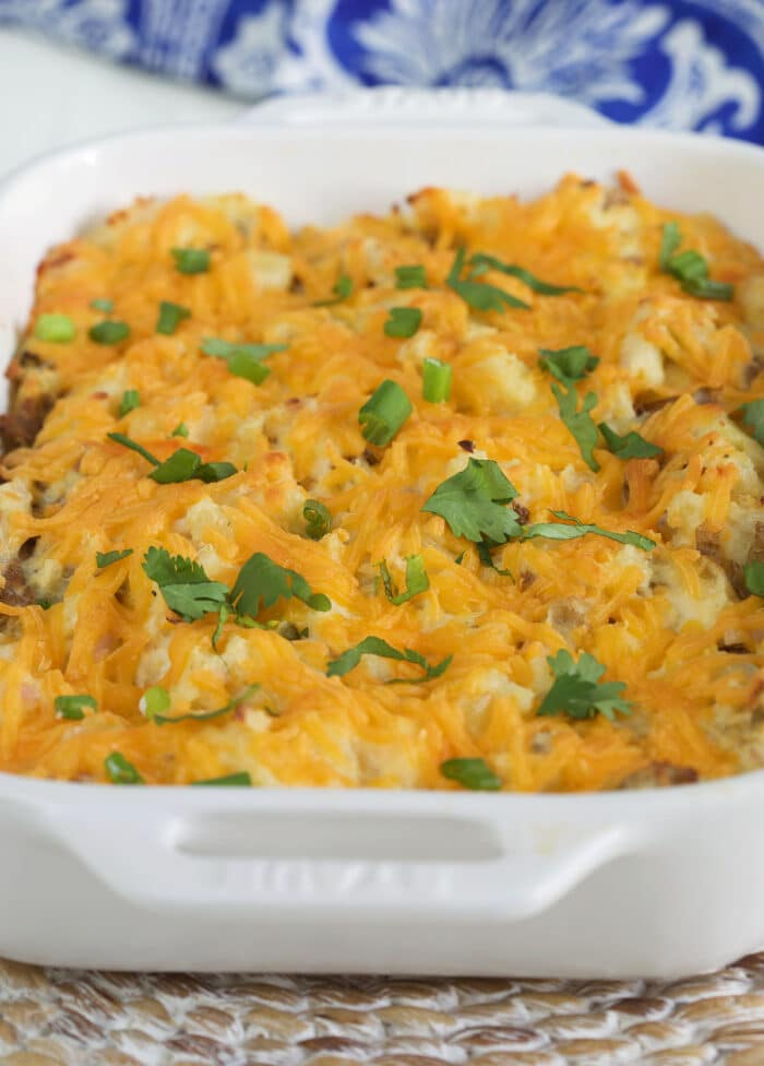 Baked potatoes and cheese are in a casserole dish.
