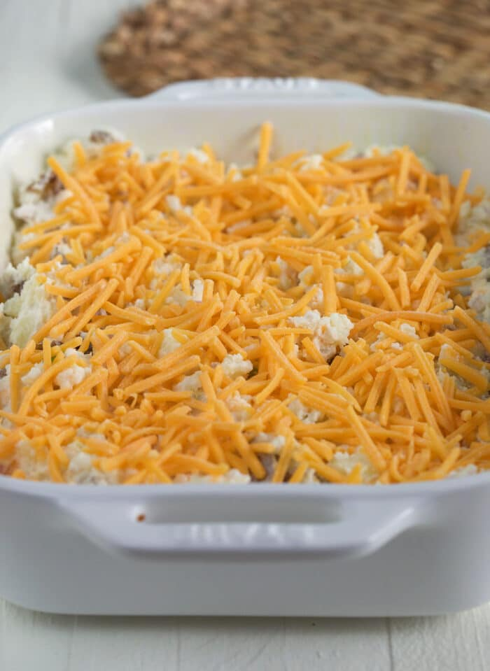 Shredded cheddar cheese is on top of potatoes in a white casserole dish.