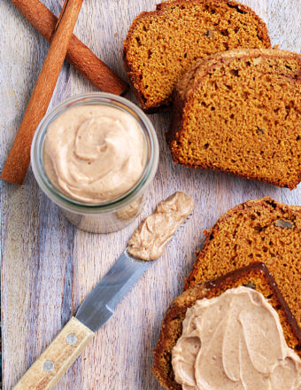 Cinnamon sticks are placed next to a sliced loaf of bread and a jar of Texas Roadhouse butter.