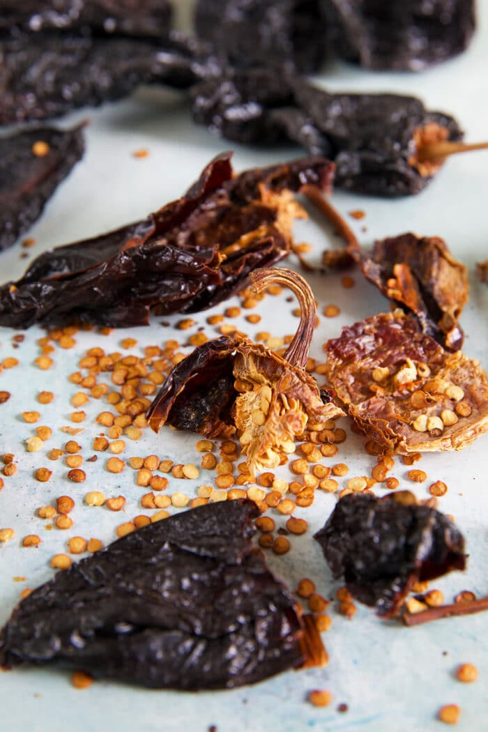 Ancho chilis are broken on a white surface, revealing many seeds.