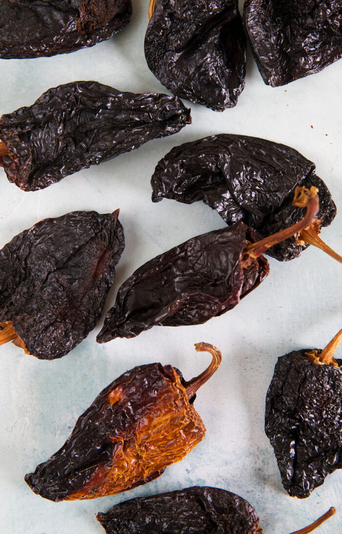 Dried whole ancho chilis are placed on a white surface.